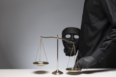 Man holding black evil mask in one hand pressing the scale on the gray background with invisible face, scale on the wooden desk, Concepts of law and justice. Foto de archivo
