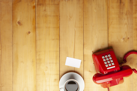 Top view of red old telephone, name card and a cup of coffee on wooden floor , wood texture background, natural pattern wood background. Imagens
