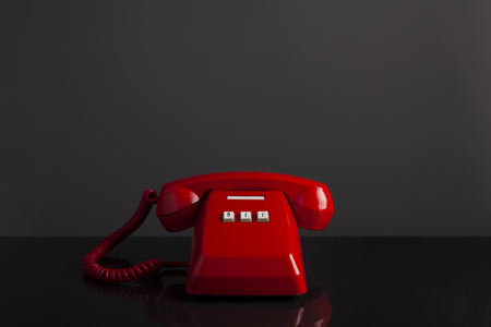 Emergency call 911 on the telephone, red old vintage telephone on black background and desk, emergency call concept.