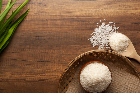 Top view of jasmine rice in a bowl and wooden spoon on dark wooden table with red flowers. Stock Photo