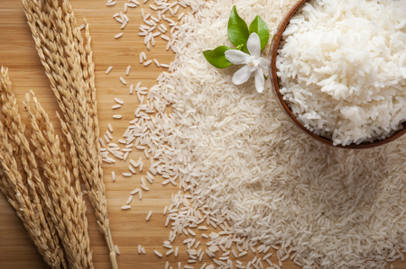 Top view of jasmine rice in a bowl on dark wooden table with rice plants, jasmine flower, ear of rices with jasmine rice in a bowl , rice scatter on the floor.