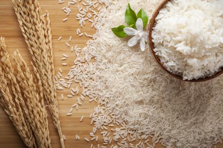 Vue de dessus du riz au jasmin dans un bol sur une table en bois sombre avec des plants de riz, fleur de jasmin, épi de riz avec du riz au jasmin dans un bol, dispersion de riz sur le sol.