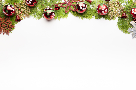 Top view of Christmas background, template with decorations of balls, gift boxes, white bells on fir tree on with white background with copy space, ornaments for new year greetings. Фото со стока