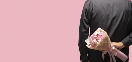 Groom wearing black shirt holding bouquet behind his back on pink background, man hiding flowers to surprise, anniversary, happy birthday. Imagens