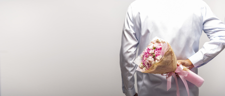 Groom wearing blue shirt holding bouquet behind his back on white background, man hiding flowers to surprise, anniversary, happy birthday. Фото со стока