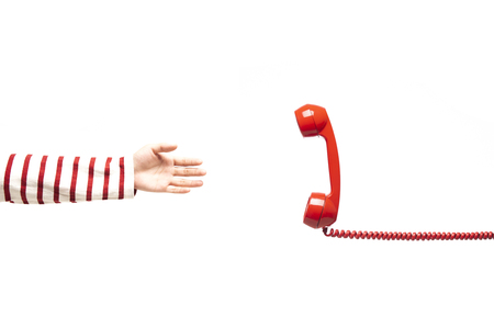 Hand reaching to the red telephone, phone calling isolated on white background, handset floating on white background.