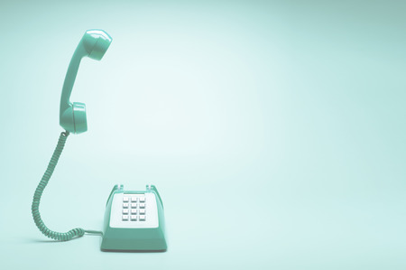 Retro green telephone on teal green background, Pop art or retro style.