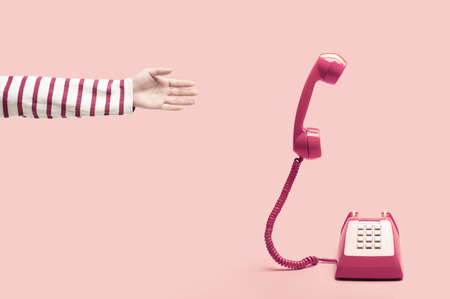 Hand reaching to the pink retro telephone, phone calling on pink background, handset floating on pink background. concept of sale or deal