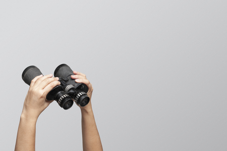 Hands holding binoculars on gray background, looking through binoculars, journey, find and search concept.