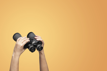 Hands holding binoculars on yellow background, looking through binoculars, journey or business find and search concept.