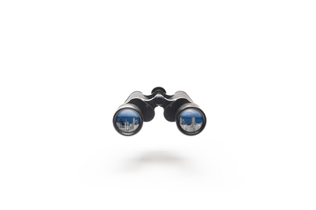 View of towers citys or buildings reflected in the lens of binoculars on white background with texting space, business searching or finding concepts.