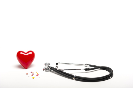 Front view of plastic red heart, stethoscopes, and drugs on white background, medical and healthy concept.