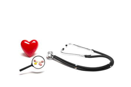 Front view of plastic red heart model, stethoscopes, and drugs with magnifying glass on white background, medical and healthy concept. Фото со стока