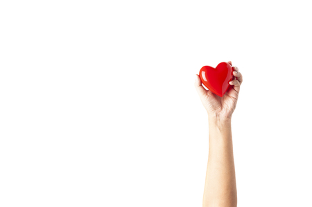 Hand holding plastic red heart isolated on white background, raising hand with red heart. happy healthy concepts