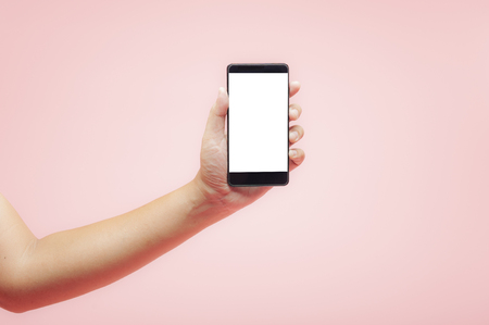 Hand holding smartphone with white blank screen on pink background, technology concept.
