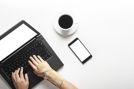Top view of hands with wrist pain from using computer, office syndrome hand pain, a cup of coffee and smart phone beside the laptop. woman use elastic bandage to treating.