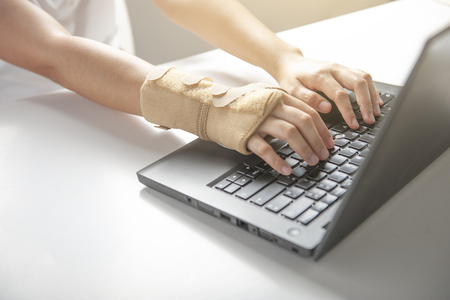 Wrist pain from using computer, office syndrome hand pain or injury, woman use elastic bandage to treating.