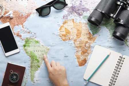 Top view of world map, sunglasses, binocular and passport with texting space, travelling concept, plan a trip, Itinerary planner, one hand point to the map.