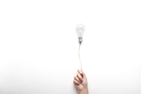 Hand holding  light bulb on rope floating on white background with texting space, idea concept.