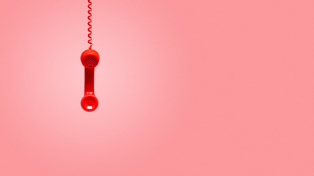 Red old telephone receiver hanging on pink background with texting space, waiting for phone call, vintage telephone. Фото со стока