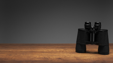 Vintage black binoculars on wood table and gray background with texting space, travelling concept.