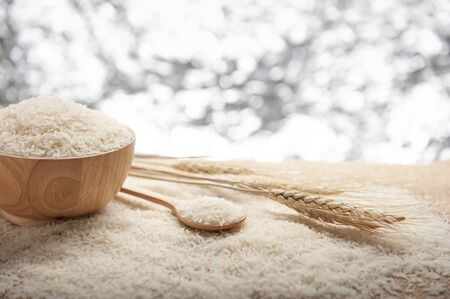 Jasmine rice in a wooden bowl,  spoon and  ear of rice on wooden background and bokeh backdrop , organic concept.