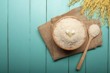 Top view of jasmine rice with jasmine flower on top in a wooden bowl,  spoon and  ear of rice, with green wooden background, organic concept.