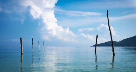 groynes: Cloudy sky over the sea at sunrise. Old wooden fishermens jetty. Beautiful minimalistic serene scene.