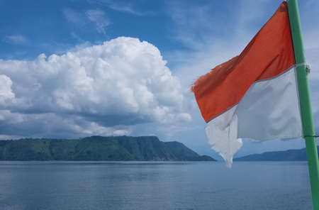 Flag of Indonesia flying with cloudy landscape at the background, Lake Toba, North Sumatra. Stock Photo