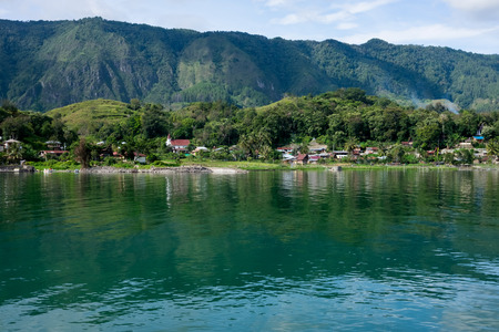 View to Samosir Island from Tuk-Tuk peninsula with nice reflections in the Lake Toba, North SUmatra, Indonesia Stock Photo