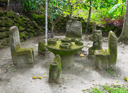 rupestrian: Ancient Indonesian sculptures of backchairs and table carved from stone, at Ambarita Stone Chairs worship, Lake Toba, Samosir, Indonesia