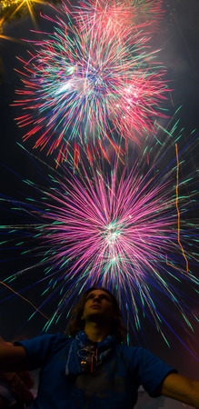 Young man is looking up to the sky for Colorful Fireworks Stock Photo