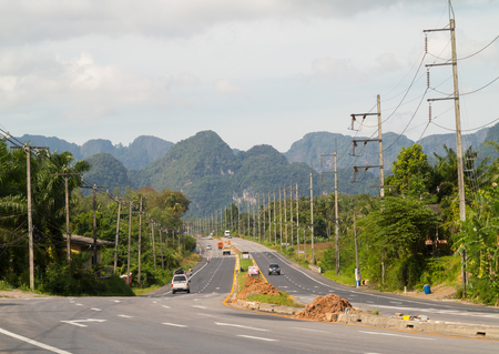 Highway road with mountains landscape at the background, Thailand.