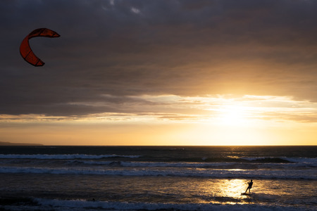 kuta: Silhouette of a kitesurfer riding at sunset with cloudy sky on the background, Kuta, Bali, Indonesia Stock Photo