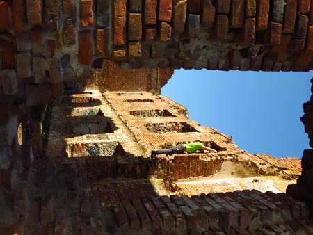 A young diver climbing the old brick wall photo
