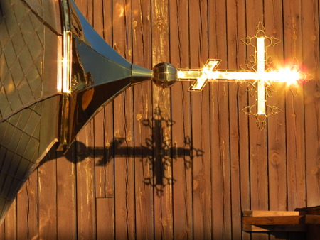 gold cross: Christian gold  cross with shadow on wall