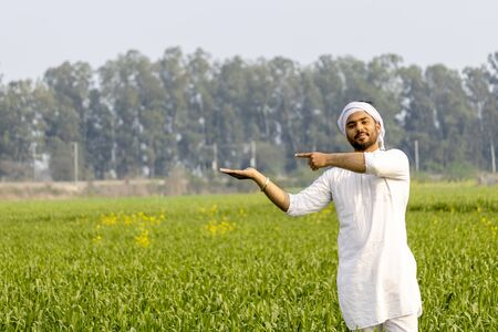 Indian farmer with empty hand for product putting and pointing finger at empty hand