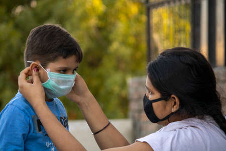 Indian child coughing on his elbow showing tips to protecting corona virus