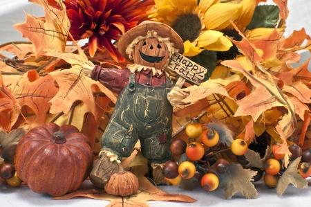 espantapajaros: Figura de Halloween sosteniendo signo con fondo de caída de hojas y flores Foto de archivo