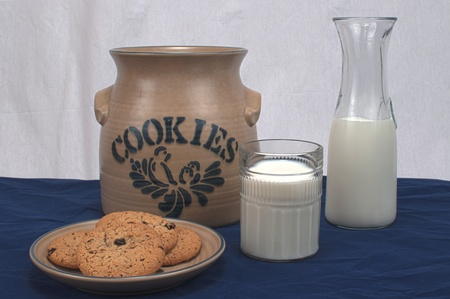 milk and oatmeal cookies on blue and white background