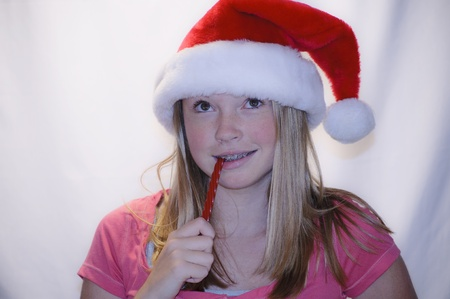 far away look: Young girl in santa hat eating candy with far away look Stock Photo