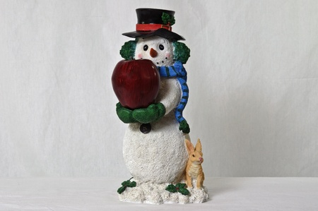 snowman holding apple with rabbit sitting at base photo