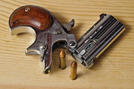 handgun: silver 22 magnum derringer on wood background Stock Photo