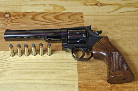 357 Magnum revolver with bullets on wood background