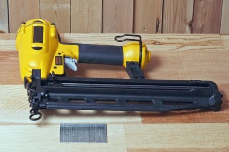 yellow nail gun and nails on wood background photo