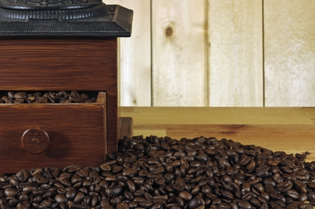 old coffee grinder and coffee beans on wood