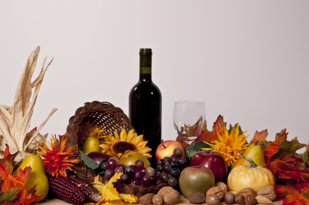 cornucopia of fruits gourds and nuts with wine glass and bottle of red wine