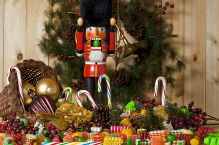 the nutcracker: nutcracker soldier with sour ball in mouth surrounded by a cornucopia of christmas candy Stock Photo