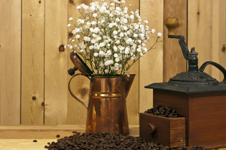 antique coffee grinder coffee beans and copper pitcher on wood background Reklamní fotografie