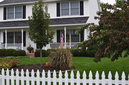 colonial house: Classic two story colonial home white with black shutters porch and picket fence